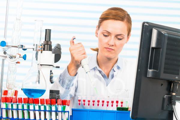 Female chemist using pipette in lab