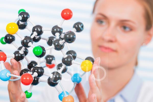 Female chemist examining molecular model