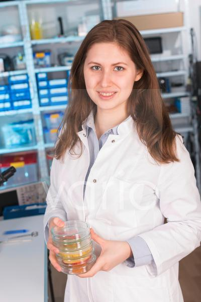 Lab technician holding petri dishes