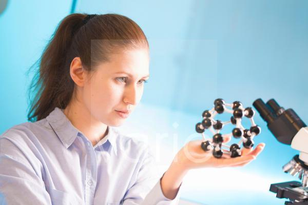 Lab technician holding atomic model