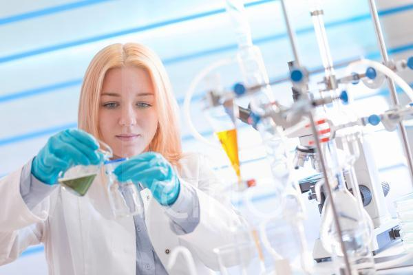 Lab technician pouring chemical