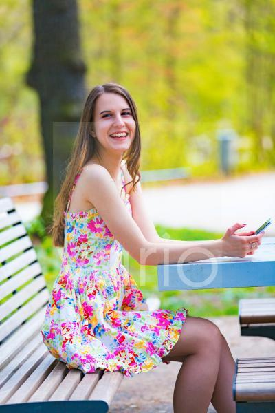 Woman on park bench with mobile phone