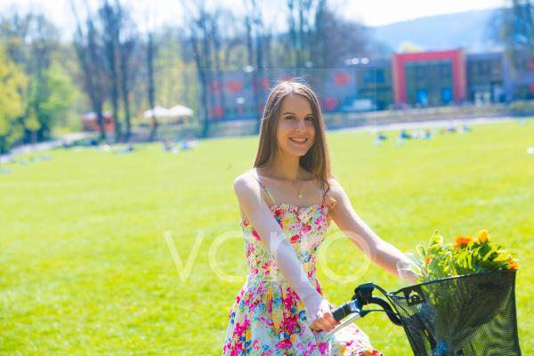 Woman on bicycle with flowers in basket