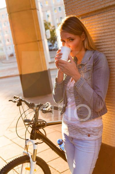Woman drinking coffee with bicycle