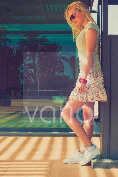 Woman wearing mini skirt standing by wall
