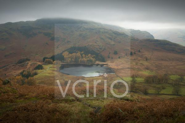 Blea Tarn and Wrynose Fell from Lingmoor Fell on a misty autumnal day in the English Lake District National Park.