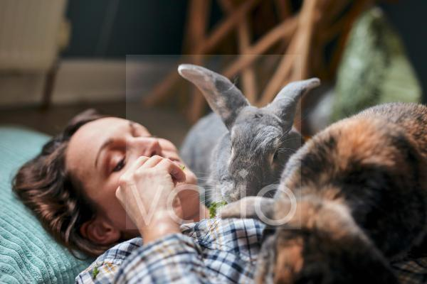 Woman lying on the floor feeding two pet house rabbits