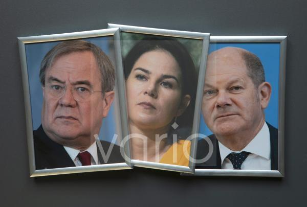 Illustrtaion photo on the subject of the 2021 federal election. Framed portrait photos of Armin Laschet, Annalena Baerbock and Olaf Scholz.