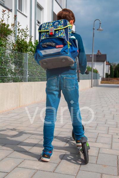 Symbolbild Schulkind mit Tretroller auf dem Schulweg model released