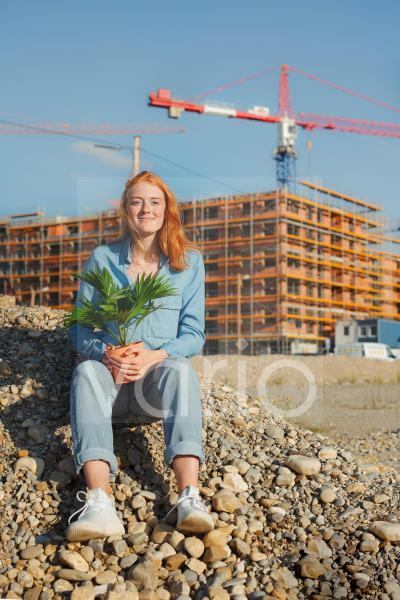 Young woman sitting with potted plant on pile during sunny day