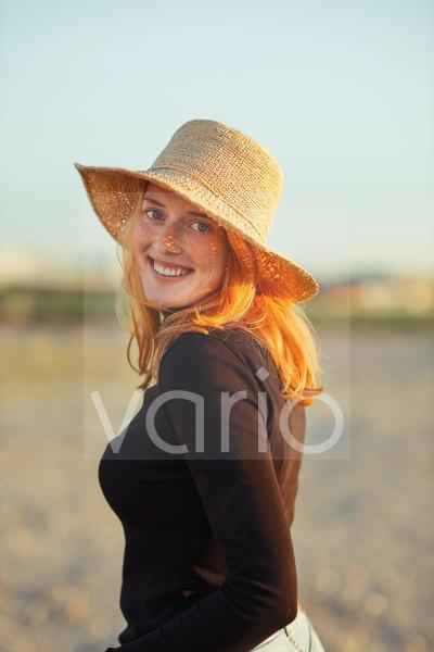 Smiling redhead woman wearing hat at sunset