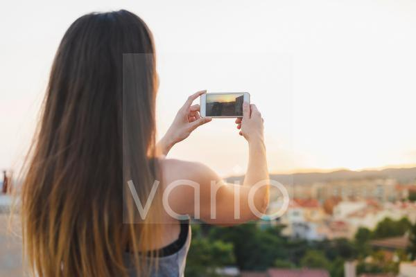 Woman photographing sunset view through smart phone at rooftop