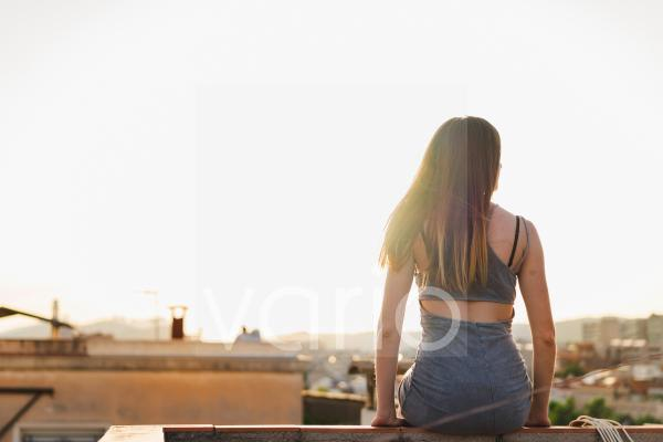 Young woman sitting on retaining wall during sunset