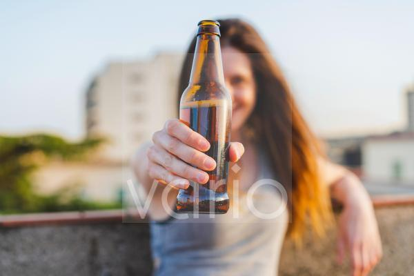 Young woman holding beer bottle at rooftop
