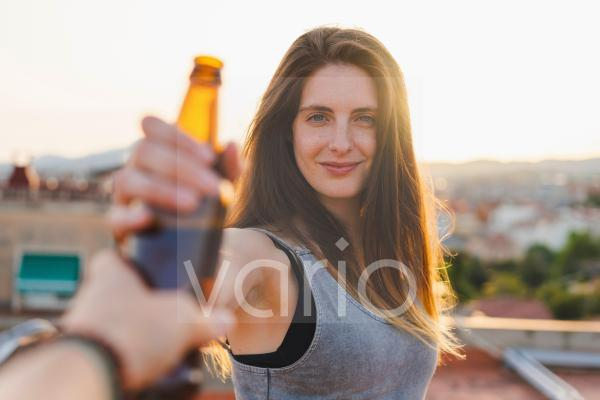 Smiling woman taking beer bottle from friend at rooftop