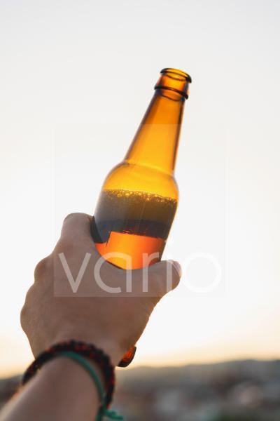 Man holding beer bottle during sunset