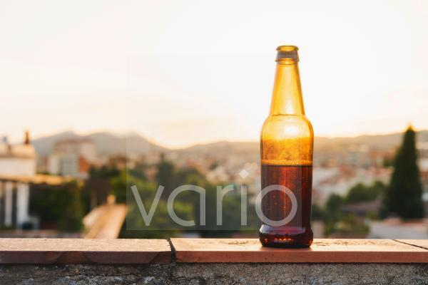 Beer bottle on retaining wall during sunset