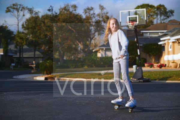 Smiling girl skating on road