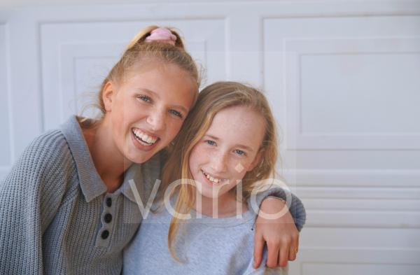 Happy girls embracing in front of door