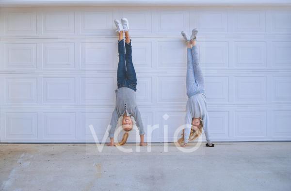 Girls doing handstand in front of garage door