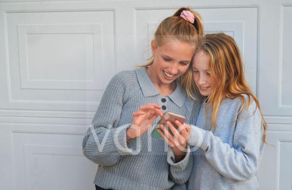 Smiling girls sharing mobile phone in front of garage door