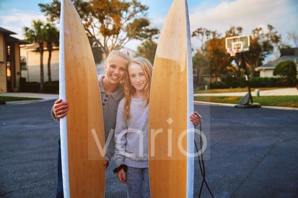 Smiling girls holding surfboards in public park
