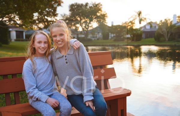 Smiling girls sitting on bench by pond