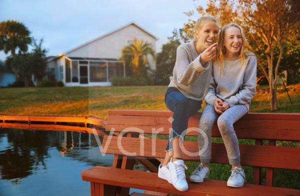 Happy girl gesturing while sitting with friend on bench