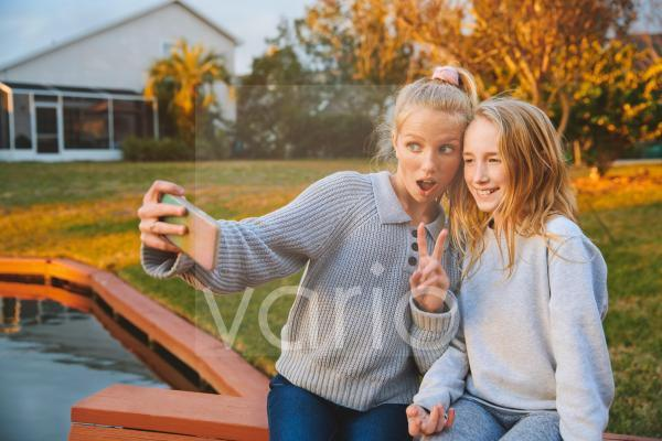 Girl with mouth open gesturing while taking selfie with friend through smart phone by pond