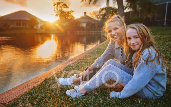 Happy girls sitting on grass by pond during sunset