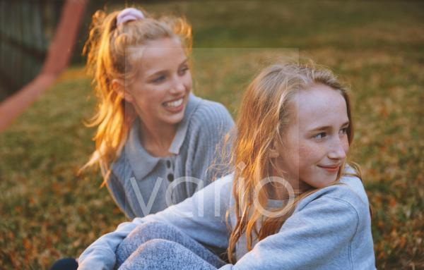 Girls looking away while sitting on grass in park