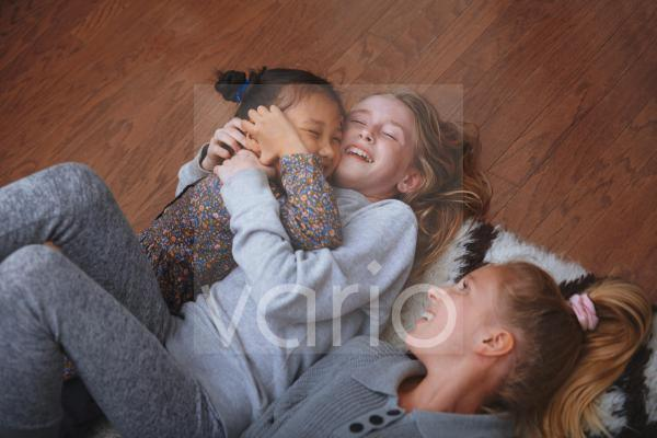 Happy girls having fun while lying on floor at home
