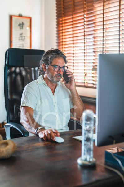 Male freelancer talking on mobile phone while using computer at home