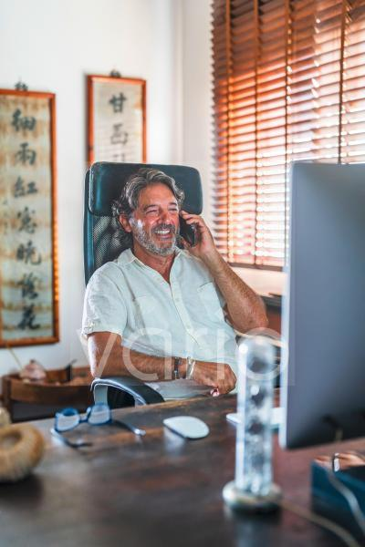 Smiling male freelancer talking on mobile phone at home