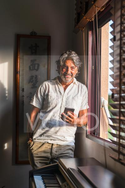 Smiling man with mobile phone standing by window