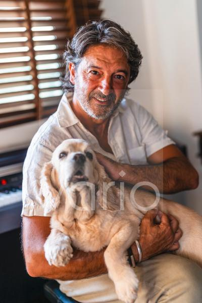 Man holding dog while sitting at home