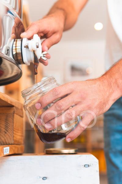 Male entrepreneur pouring honey in jar at shop