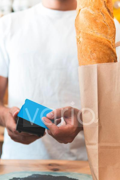 Male entrepreneur taking payment through credit card at counter in retail shop