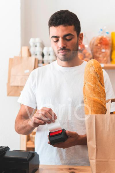 Young male shop owner removing receipt from reader at checkout counter