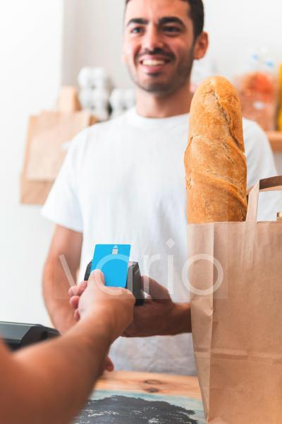 Male customer paying through credit card to owner at shop