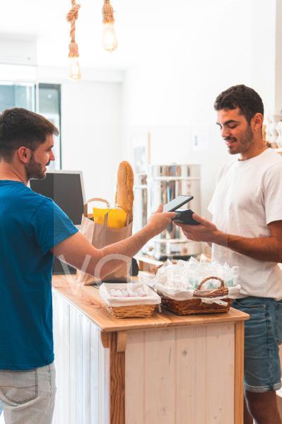 Male customer paying through smart phone at retail shop