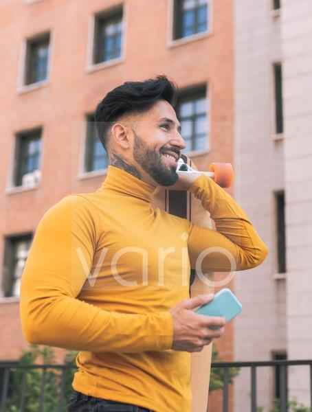 Smiling bearded man with mobile phone carrying skateboard