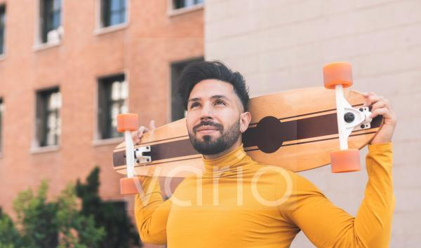 Thoughtful man with skateboard on shoulders