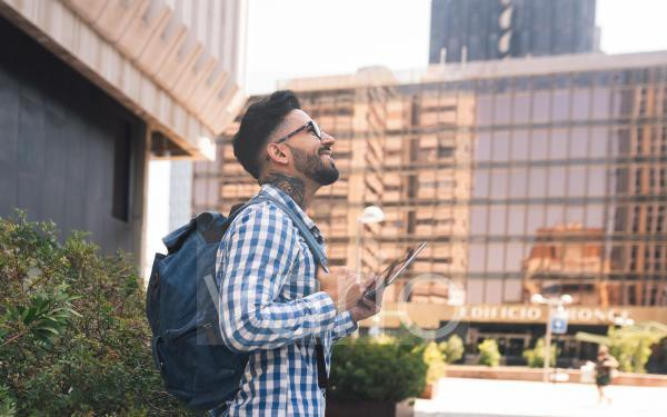 Smiling man with backpack holding digital tablet in city