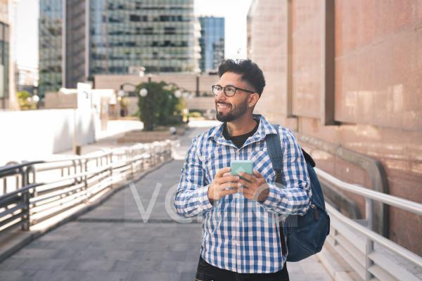 Smiling man with mobile phone and backpack in city