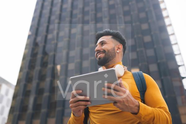 Smiling man holding digital tablet in front of skyscraper