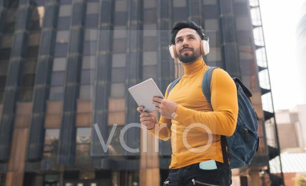 Handsome man listening music holding digital tablet in city