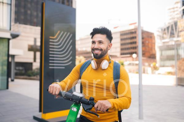 Smiling man with electric push scooter in city