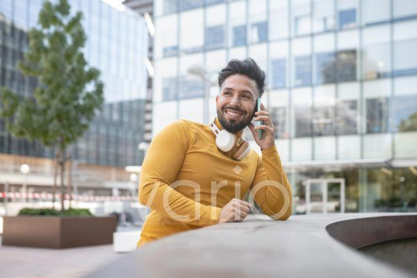 Smiling man talking on mobile phone in city