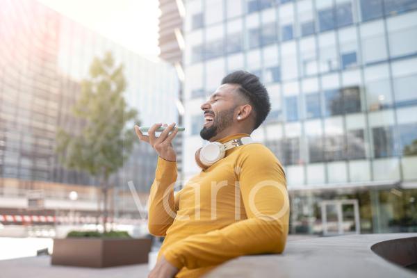 Cheerful man talking through smart phone in city